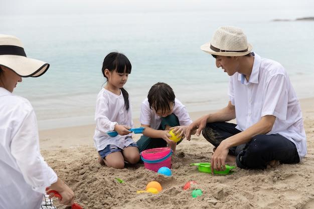 Glückliche asiatische familie vier leute im sommerurlaub, die zusammen spielzeug auf sand im strand spielen in der morgenzeit sonnenaufgang. urlaubs- und reisekonzept.