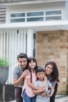 Glückliche asiatische familie vor ihrem haus