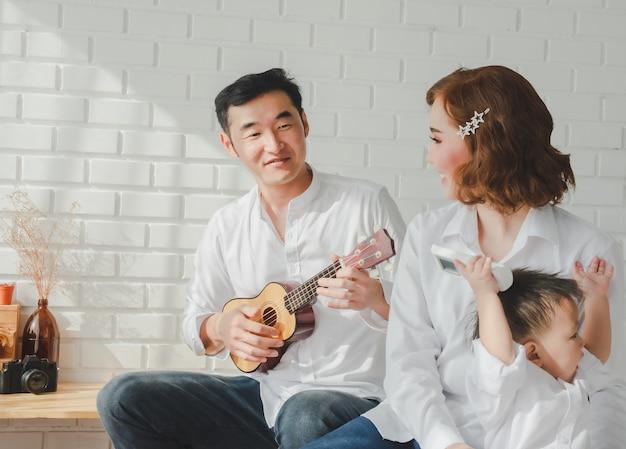 Glückliche asiatische familie zu hause, vater, der ukulele spielt