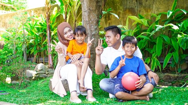 Glückliche asiatische familien, die zusammen im park spielen und fotografieren
