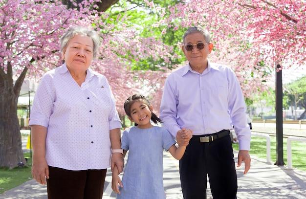 Glückliche asiatische familiengeneration mit großeltern und kind auf öffentlichem park