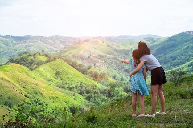 Glückliche asiatische familienmutter und -tochter, die auf den schönen berg hält angehobene hände steht