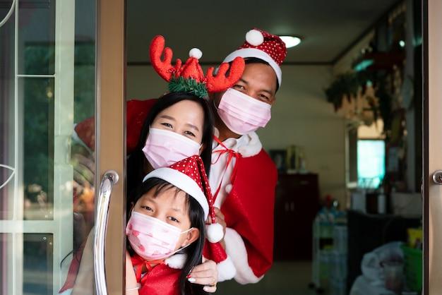 Glückliche asiatische familientochtermutter und -vater tragen gesichtsmaske am weihnachtstag
