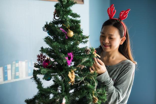 Glückliche asiatische frau am weihnachtsbaum