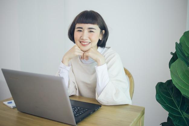 Glückliche asiatische frau arbeiten von zu hause aus