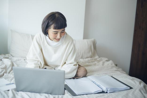 Glückliche asiatische frau arbeitet im schlafzimmer. sie arbeitet von zu hause aus.