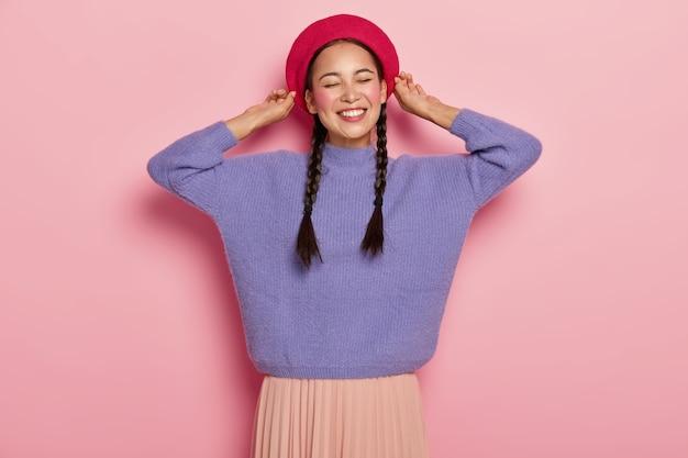 Glückliche asiatische frau berührt baskenmütze, lächelt angenehm, zeigt weiße zähne, hat zwei zöpfe, trägt lila pullover und rock, drückt angenehme gefühle aus, isoliert über rosa wand