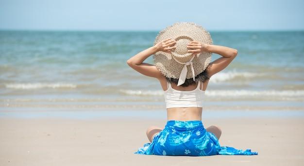 Glückliche asiatische frau, die am strand lächelt und spaß hat