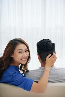Glückliche asiatische frau, die auf couch mit ehemann sitzt und sich herum dreht, um kamera zu betrachten