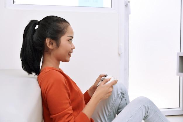 Glückliche asiatische frau, die auf dem boden sitzt und videospiele spielt