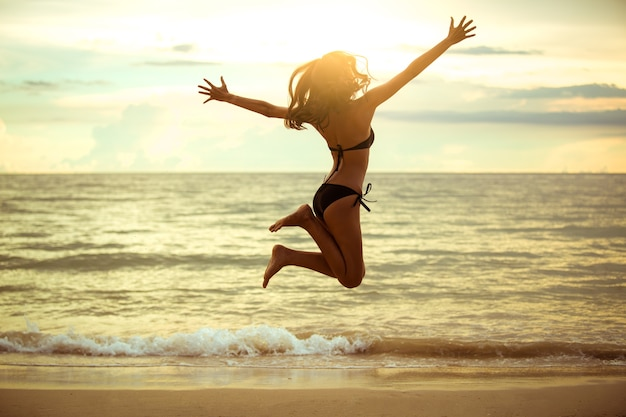 Glückliche asiatische frau, die auf den strand springt