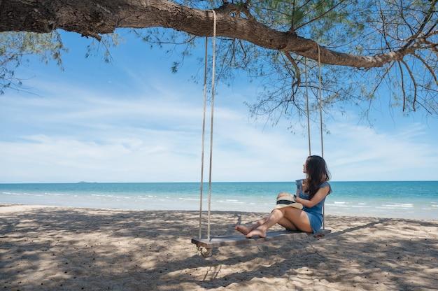 Glückliche asiatische frau, die auf hölzerner schaukel am strand im tropischen meer ruht