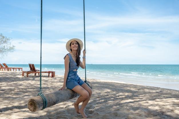 Glückliche asiatische frau, die auf hölzerner schaukel am strand im tropischen meer sitzt.