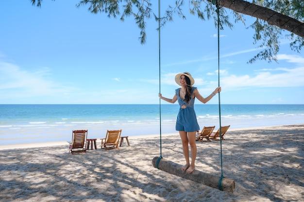 Glückliche asiatische frau, die auf hölzerner schaukel am strand im tropischen meer steht