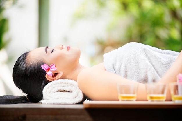 Glückliche asiatische frau, die auf massagetabelle liegt