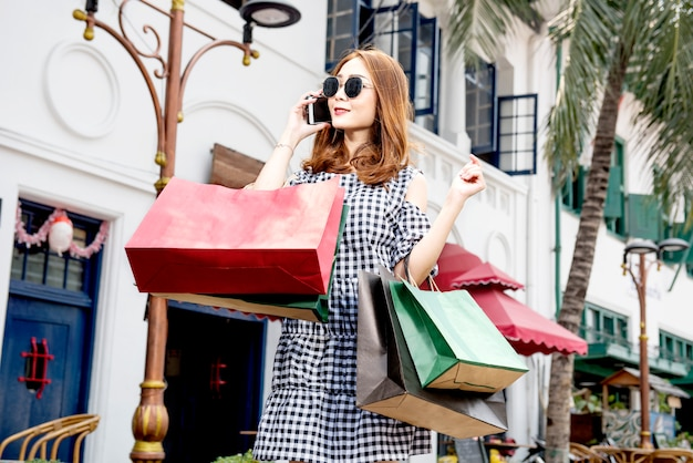 Glückliche asiatische frau, die auf smartphone beim tragen von einkaufstaschen spricht