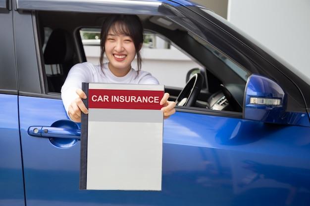 Glückliche asiatische frau, die autoversicherungsdokumentbuch hält und im auto, sicherheitsfahrzeug- und schutzkunden-personenkonzept sitzt