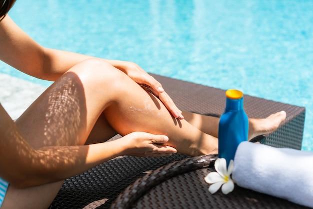 Glückliche asiatische frau, die badeanzug trägt, hut, der auf sonnenliege liegt, sonnencreme aufträgt und sich am pool entspannt.
