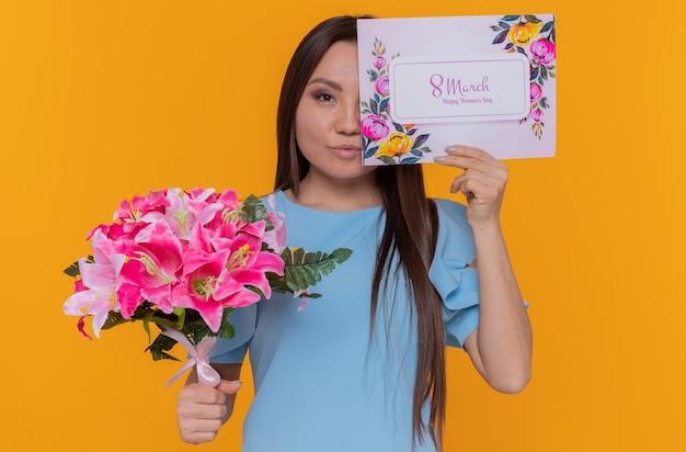 Glückliche asiatische frau, die begrüßung hält, die ein auge mit karte hält, die blumenstrauß hält, der internationalen frauentagsmarsch feiert