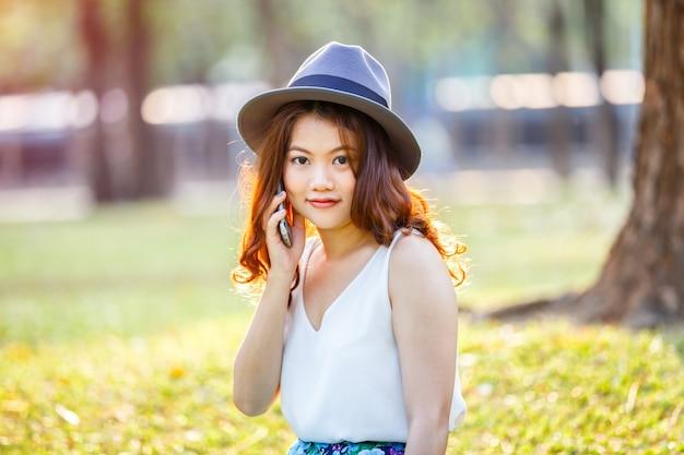 Glückliche asiatische frau, die den smartphone im freien, asiatische schönheit spricht