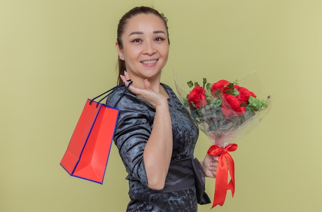 Glückliche asiatische frau, die den strauß der roten rosen und der papiertüte mit dem geschenk hält, das fröhlich betrachtet front betrachtet, der internationalen frauentag feiert, der über grüner wand steht
