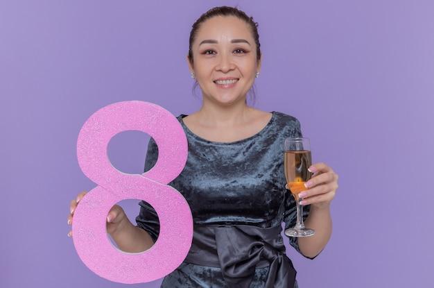 Glückliche asiatische frau, die die nummer acht hält, die aus pappe und einem glas champagner gemacht wird, die vorne lächelnd fröhlich feiern, den internationalen frauentag über lila wand stehen