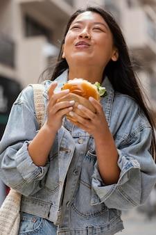 Glückliche asiatische frau, die einen burger draußen isst