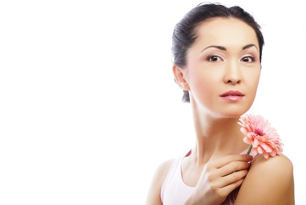Glückliche asiatische frau, die einen rosa gerbera hält