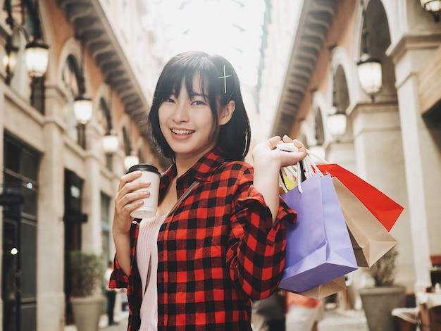 Glückliche asiatische frau, die einkaufstasche hält.
