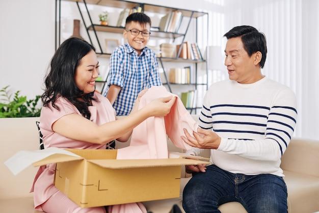 Glückliche asiatische frau, die hellrosa kleid aus geschenkbox von ihrem ehemann und jugendlichen sohn nimmt