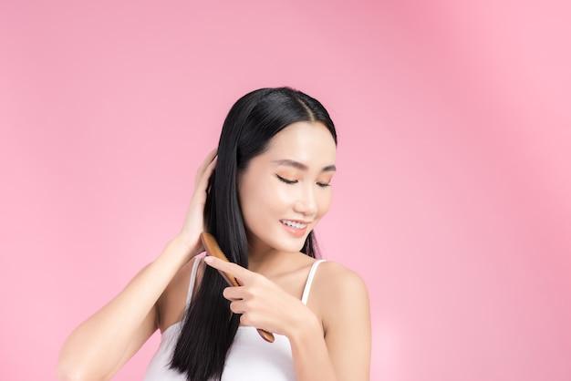 Glückliche asiatische frau, die ihr schönes schwarzes haar kämmt. getrennt auf rosa.