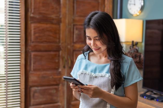 Glückliche asiatische frau, die ihre e-mail-nachricht auf ihrem telefon überprüft, während sie zu hause bleibt