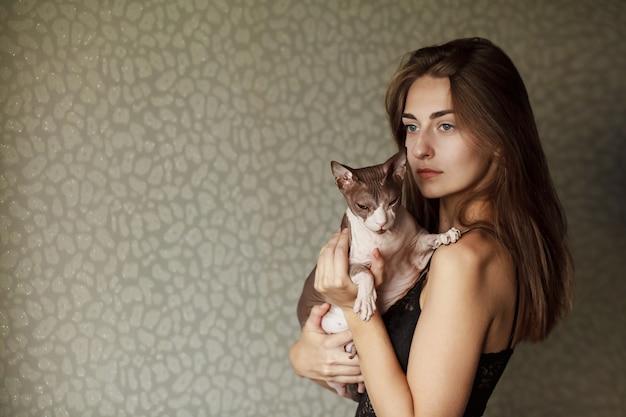 Glückliche asiatische frau, die ihre sphynx katze anhält