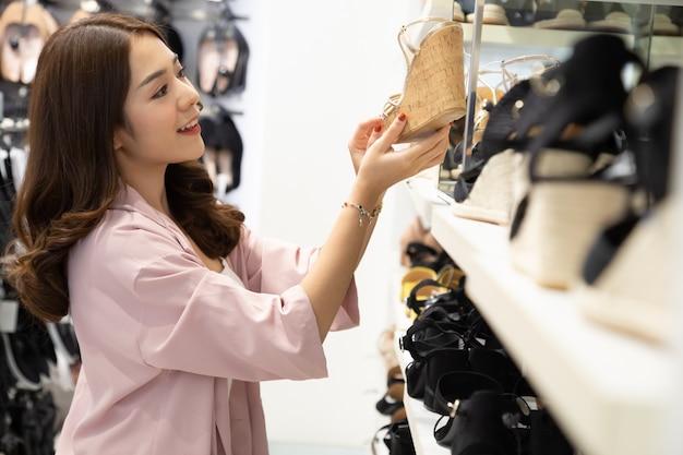 Glückliche asiatische frau, die im schuhgeschäft mit dem genuss des heißen verkaufsendes ende der saison im einkaufszentrum genießt