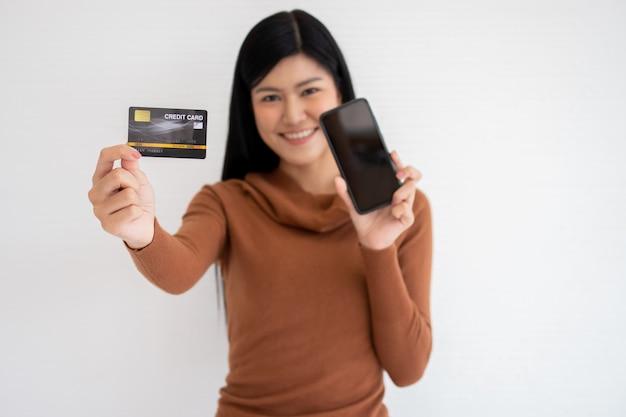 Glückliche asiatische frau, die kartenkredit und smartphone hält