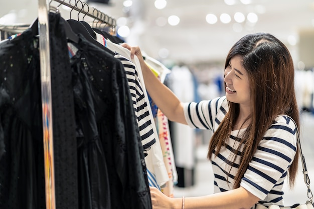 Glückliche asiatische frau, die kleidung im glasgeschäftshop mit glücklicher aktion in der abteilung mitte wählt