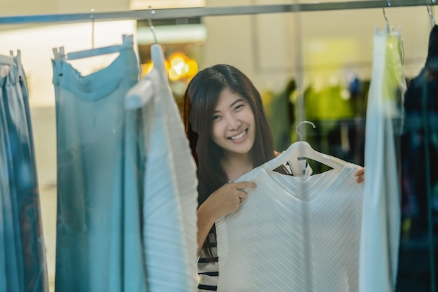 Glückliche asiatische frau, die kleidung im glasladenshop mit glücklicher aktion am abteilungszen wählt