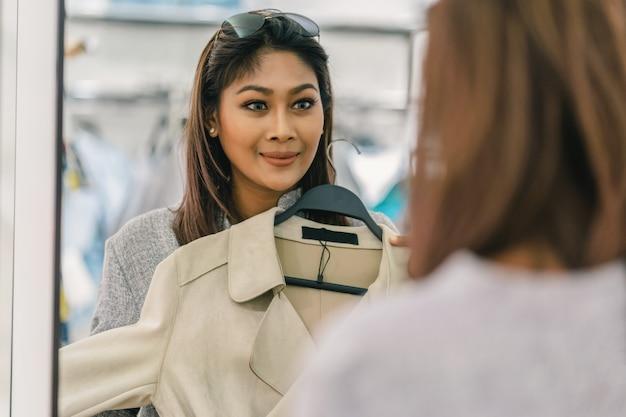 Glückliche asiatische frau, die kleidung mit reflexion des glases im geschäft am abteilungszentrum wählt