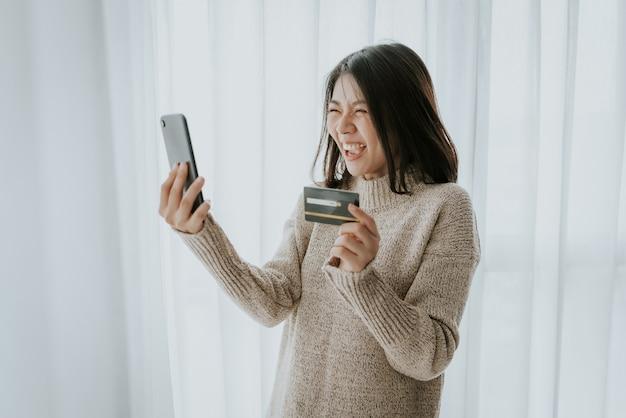 Glückliche asiatische frau, die kreditkarte für online-einkauf mit smartphone verwendet