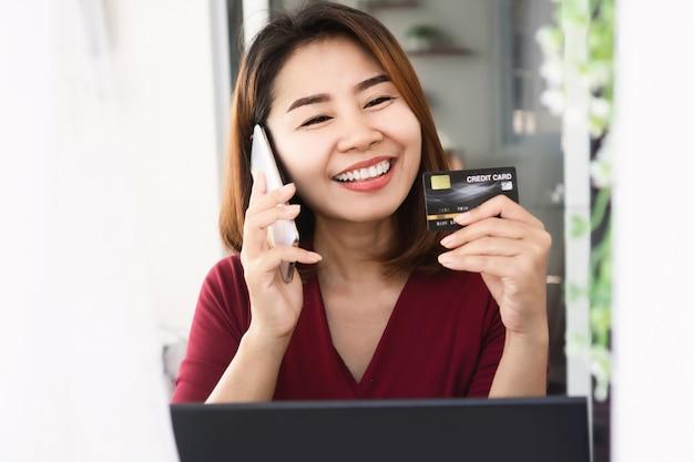 Glückliche asiatische frau, die kreditkarte hält und auf handy spricht
