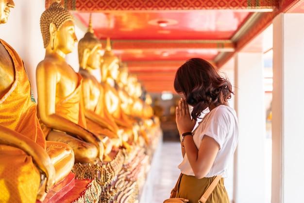 Glückliche asiatische frau, die mit buddha betet