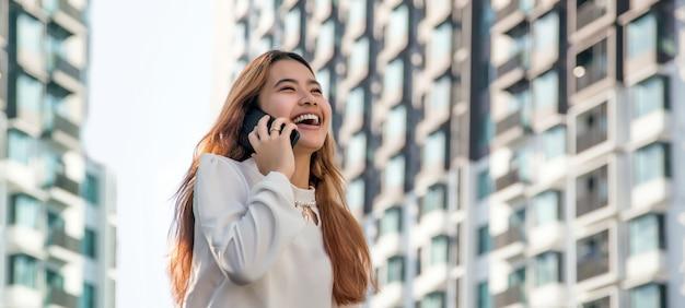 Glückliche asiatische frau, die mit handy auf hohem gebäude auf hintergrund in fahnengröße spricht