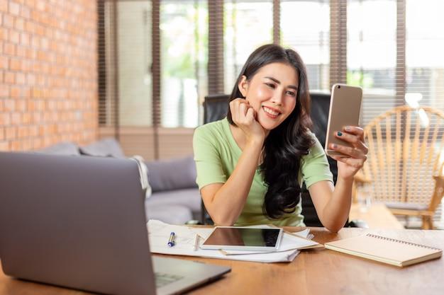Glückliche asiatische frau, die mit ihren freunden durch social-media-app auf ihrem telefon in ihrem heimbüro des wohnzimmers chattet