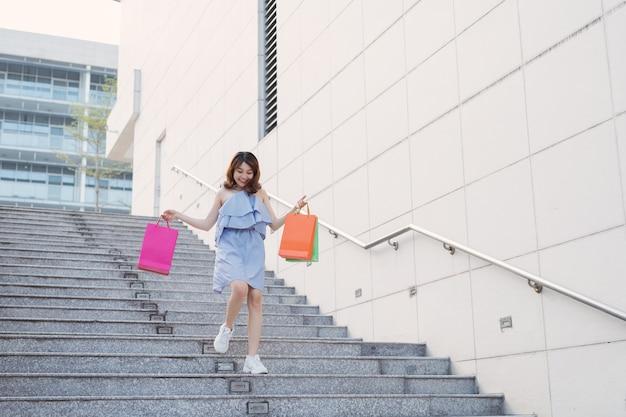 Glückliche asiatische frau, die mit zwei händen die treppe hinuntergeht, die bunte einkaufstaschen halten.