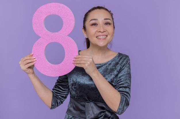 Glückliche asiatische frau, die nummer acht aus pappe hält, die kamera lächelnd betrachtet