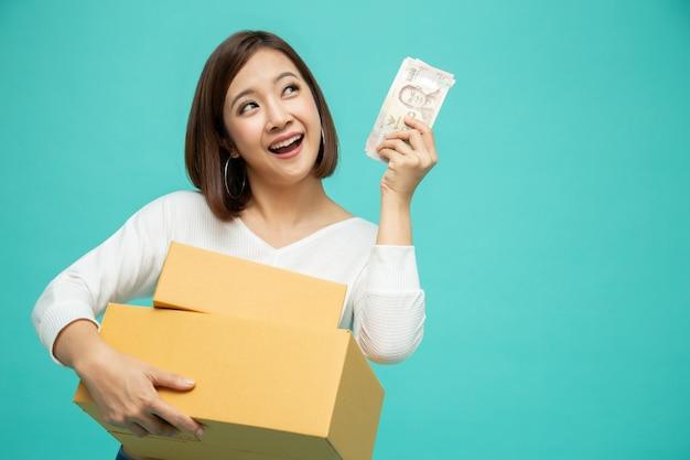 Glückliche asiatische frau, die paketpaketbox hält und mit geldbanknoten thailändischen baht lokalisiert auf grünem hintergrund, zustellkurier und versandservicekonzept feiert