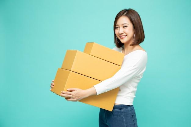 Glückliche asiatische frau, die paketpaketbox hält