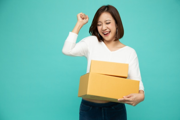 Glückliche asiatische frau, die paketpaketbox, zustellkurier und versandservicekonzept hält