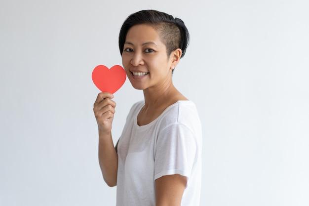 Glückliche asiatische frau, die papierherz hält