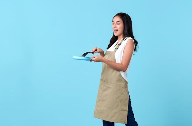 Glückliche asiatische frau, die pfanne hält, die auf blau kocht.